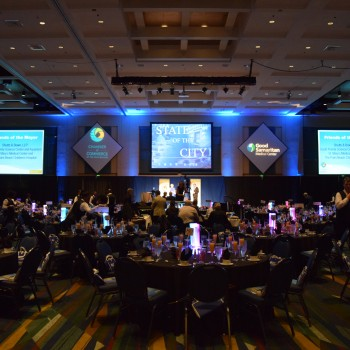 Photo of a three screen display hung from the ceiling against the wall in the front of the building with hanging event logo displays in between each screen. Screens display the Palm Beach County Mayor's Breakfast event.