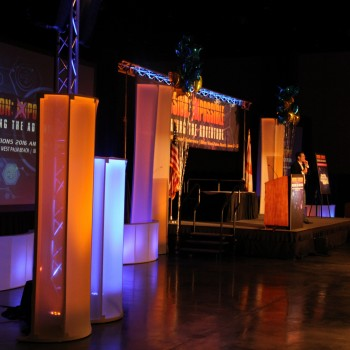 This is a photo representing a stage set-up with lighting and lit rectangular standing pillars in orange and blue around the front of the stage.