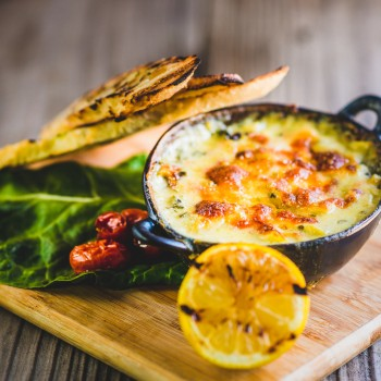 Photo of a small round cast iron skillet of cheese dip served on a small wooden cutting board garnished with a grilled lemon, Toasted French bread slices, green leaf lettuce and sun dried tomatoes