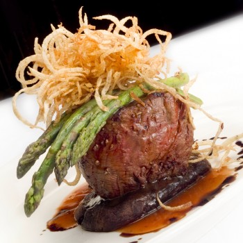 Photo of a dinner entrée with a portabella mushroom, under a filet mignon with asparagus draped over the top and topped with fried onion strings