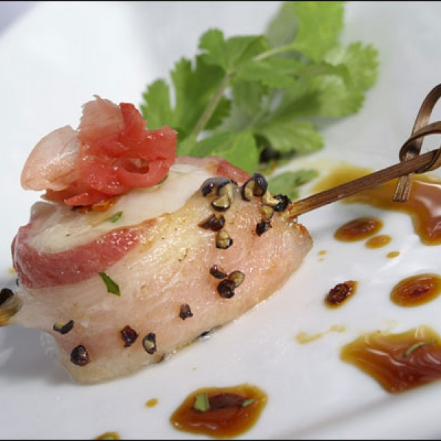 Food Photo of a bacon wrapped scallop with a decorative toothpick placed on a plate with parsley and pickled ginger garnish