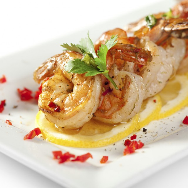 Food photo of Sautéed shrimp angled on top of one another across a bed of thinly sliced lemon wheels, garnished with red pepper relish.