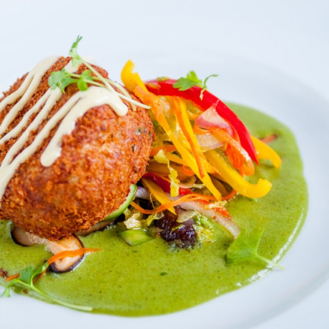 Photo of a Fried crab cake leaning on a julienne mix of red, orange and yellow peppers, on a green sauce